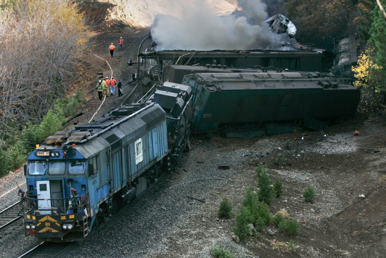 Authorities and railroad workers are seen as smoke rises from one of the derailed cars of a train maintaining Union Pacific tracks near Baxter, Calif., on Thursday.