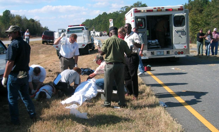 Rescuers respond to a collision between a tractor-trailer and a mule-drawn carriagenearAlapaha, Ga.m, on Saturday.