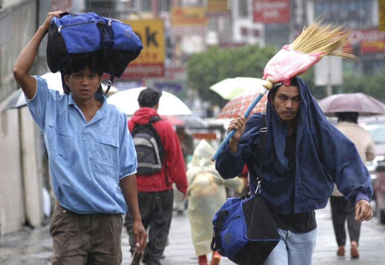 Pedestrians brave the rain in Bagu north of Manila