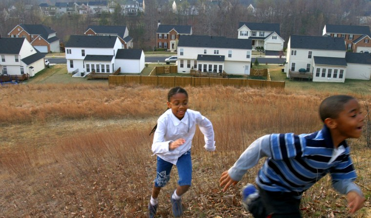Amani Moore, 8, chases her brother Ronald Moore, Jr., 7, behind their home in Dumfries, Va., in this March photo. White adults were more likely than black and Hispanic adults to have college degrees and to own their own homes, according to data released Tuesday by the Census Bureau.