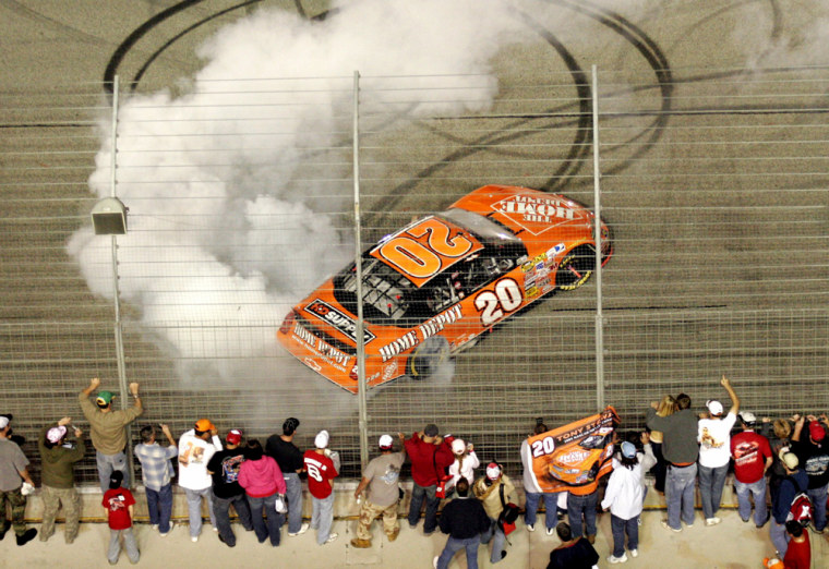 Driver Tony Stewart spins his car as he celebrates his win with fans along the fence at the Bass Pro Shops 500 NASCAR race at the Atlanta Motor Speedway in Hampton.