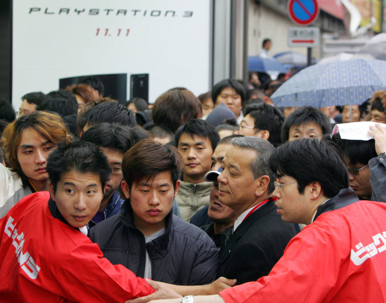 Salesclerks of Bic Camera control buyers queue up in lines to get their hands on Sony's PlayStation 3 video game consoles in Tokyo Saturday morning, Nov. 11.