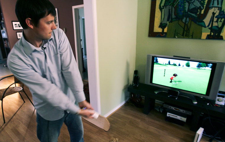 APwriterMatt Slagle demonstrates a golf swing while reviewing the Nintendo Wii game console.