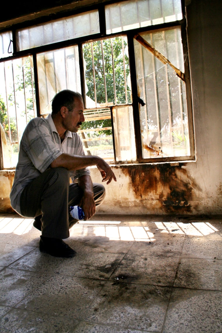 Neighbor and eyewitness Hussein Mohammed looks at the charred and blood-splattered floor and wall where he found the body of the young Iraqi girl raped then killed along with her family in their home,in thisJuly 6 photo, in Mahmoudiya, south of Baghdad.