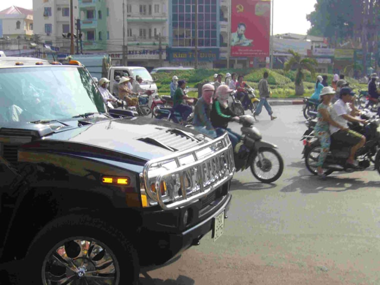 A Hummer sport utility vehicle competes with mopeds in traffic, in a sign of Vietnam's economic prosperity.