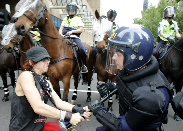 A protestor struggles to take away a police officer's baton during a demonstration at the G-20 Finance Ministers and Central Bank Governors meeting in Melbourne, Australia, on Saturday.