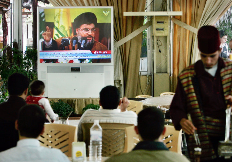 Visitors to the Sweet Land amusement park watch Hezbollah leader Hassan Nasrallah deliver a speech Sunday calling for mass demonstrations against the Lebanese government.