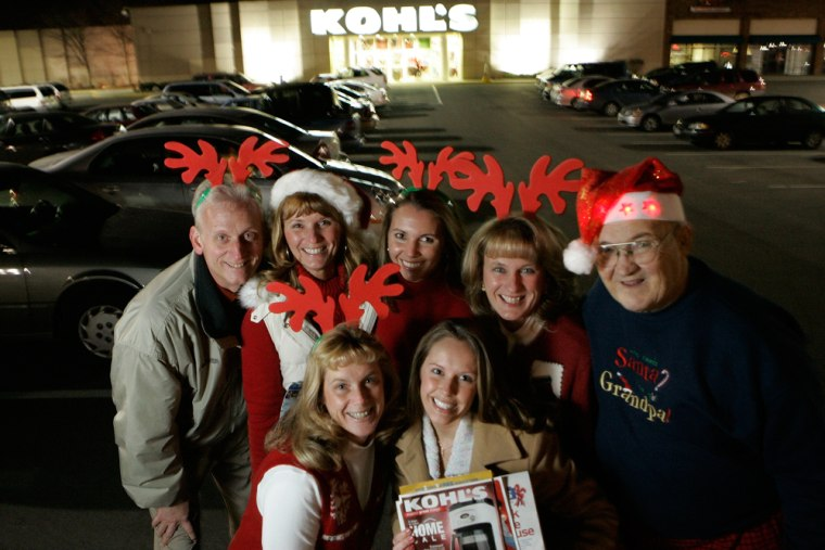 Tammy Dorion, front left, and Megan Dorion, front right, gather with their family Rick Wethrill, from back left, Sherry Dorman, Sarah Chapman, Debby Waters and Jerry Jenkins in front of a Kohl's department store, Monday in Columbus, Ohio. After they've finished their Thanksgiving feast, the family plans the next traditional gathering— shopping on Black Friday.