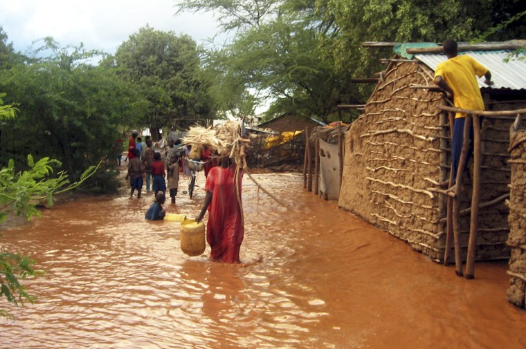 Displaced Kenyans carry their belongings though flood waters of Tana river in Garissa