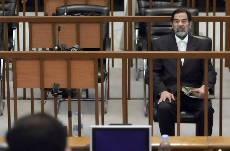 Former Iraqi leader Saddam Hussein sits in the dock during his trial inside the heavily fortified Green Zone in Baghdad