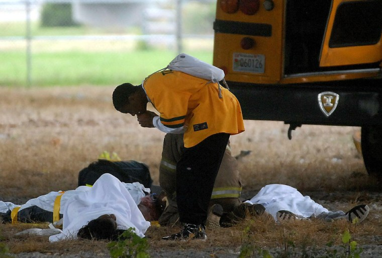 A student leans over another student from a school bus that veered off an interstate and crashed below an overpass onMonday, in Huntsville, Ala.
