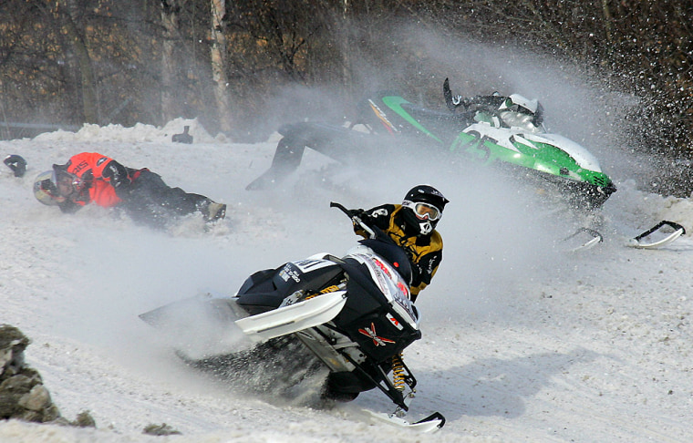 Two snowmobiles collide, knocking one rider off, as they race around the track during the Fur Rendezvous Sno-X races in Anchorage, Alaska, Feb. 26, 2005. The 17-day winter festival includes the World Championship Sled Dog races, dog weight pull, snow sculptures and other events to break up the long Alaska winter.