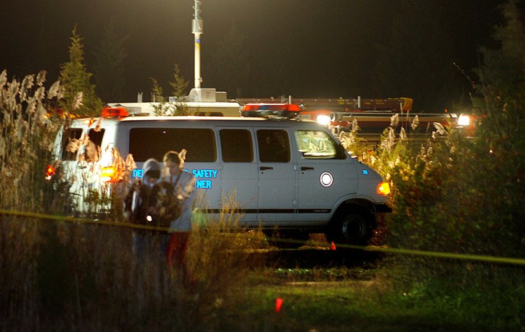 A police van moves into position to load a body at the site where four dead bodies were found in a ditch behind a motel, in Egg Harbor Township, N.J., on Monday.
