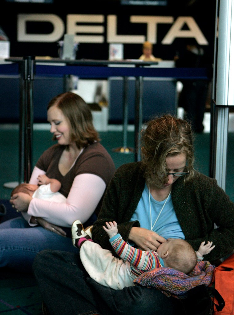 Marnie Glickman, right, breast-feeds her daughter, Calliope, while Rachel Brusseau breast-feeds her son, James, in front of the Delta Airlines gate at Portland International Airport in Portland, Ore., on Tuesday. Approximately 35 mothers with children showed up in support of a woman that was removed, along with her family, from a Delta flight in Vermont for breast-feeding her child.