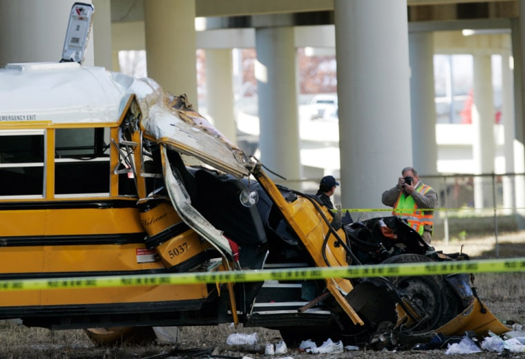 An investigator photographs the school bus that crashed Monday in Huntsville, Ala.