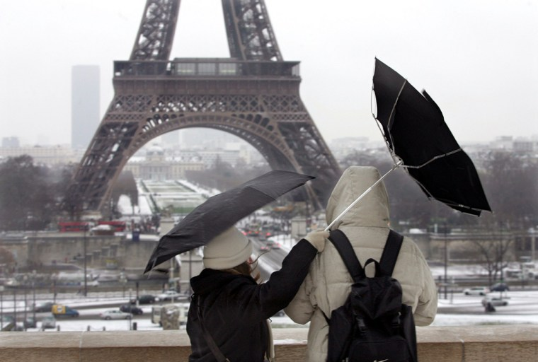 Tourists fight against gust of wind as they stand near Eiffel Tower in Paris