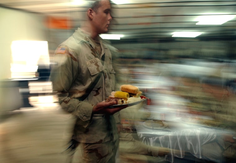 A U.S. Army 82nd Airborne Division soldier takes his Thanksgiving meal at a base in Baghdad in 2003. Many service members who are away from home on service within the United States are invited to spend the holiday with host families.
