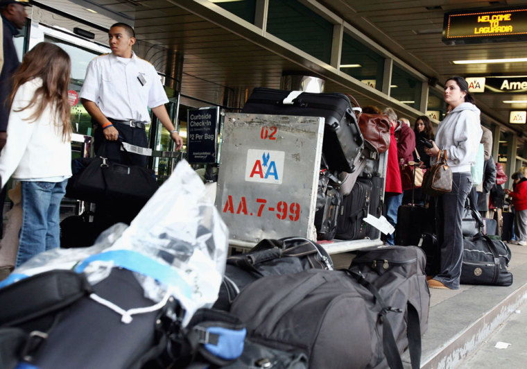 Travelers wait in line at the curbside baggage check in at LaGuardia Airport in New York