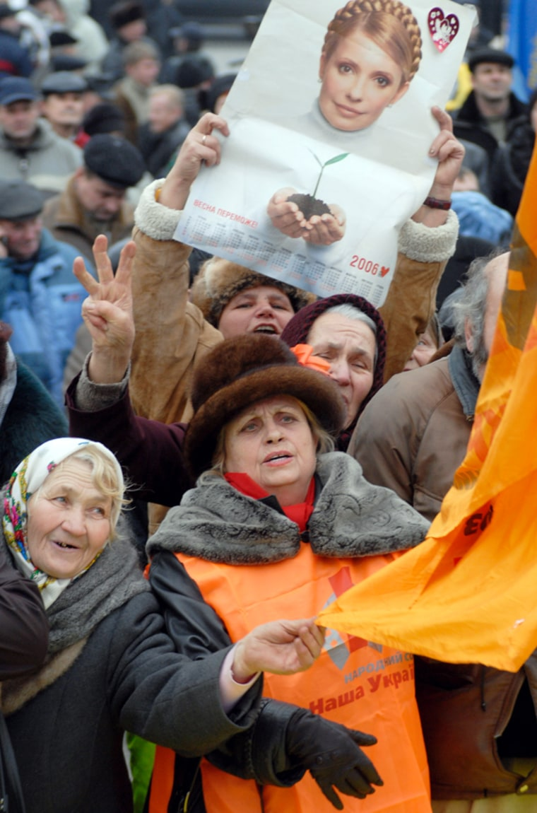 Elderly demonstrators hold an orange flag and a poster depicting former Ukrainian prime minister Yulia Tymoshenko during a rally in Kiev, Ukraine, on Wednesday, two years after afraudulent vote count led to the Orange Revolution.