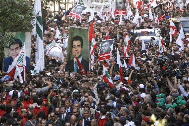 The coffin of assassinated Industry Minister Pierre Gemayel is carried by supporters as it arrives at a church in Beirut on Thursday.