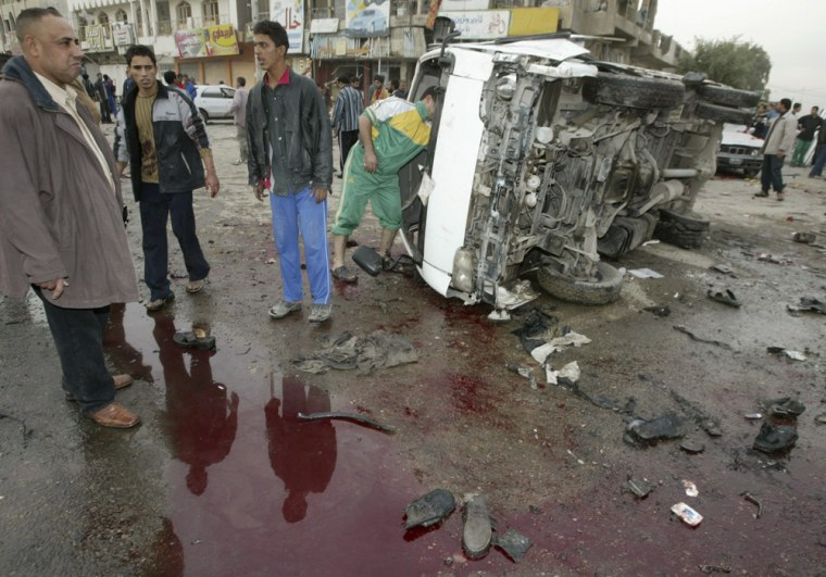 Residents stand next to a pool of bloodied water and a destroyed vehicle after bomb attacks in Baghdad's Sadr City