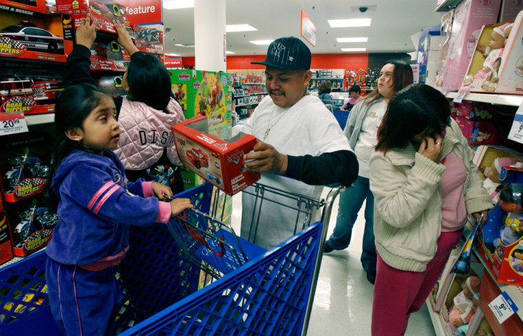 Ashley Miranda, 3, left, observes as her mother Leslie Marin, second from left, and friend Fernando Lucas, third from left, shop for toys during a Thanksgiving Day sale at a Kmartin Los Angeles.