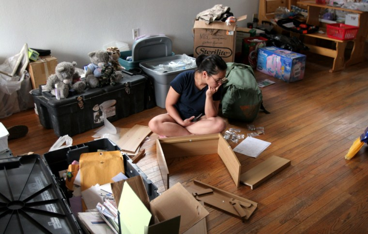 Sgt. Leana Nishimura assembles shelvingat her newly rented home inHavre de Grace, Md.Her children have been staying with her mother in Hawaii. She's unpacking and preparing the house for the arrival of her two boys, T.J., 8, and Dylan, 7, and her daughter Cheyenne, 4.