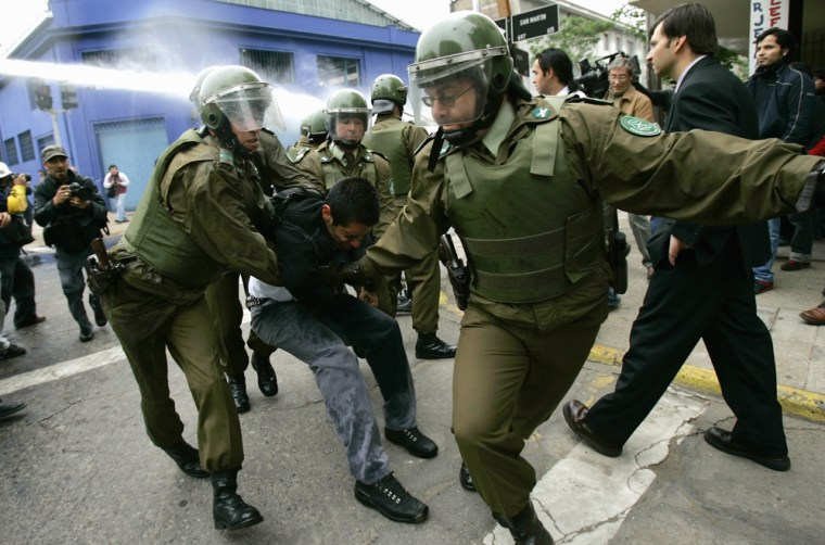 Riot police detain a high school student during a demonstration in downtown Santiago on Oct. 18. The protesters were demanding that the government accelerate promised reforms of Chile's dictatorship-era education laws.