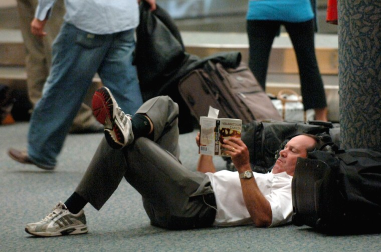 Wayne Defrancesco of Baltimore reads in the baggage claim area of the Palm Beach International Airport on Sunday.