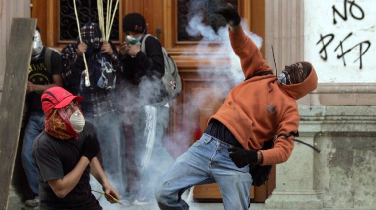 Protester throws teargas canister at federal police during clashes between demonstrators and federal police in Oaxaca