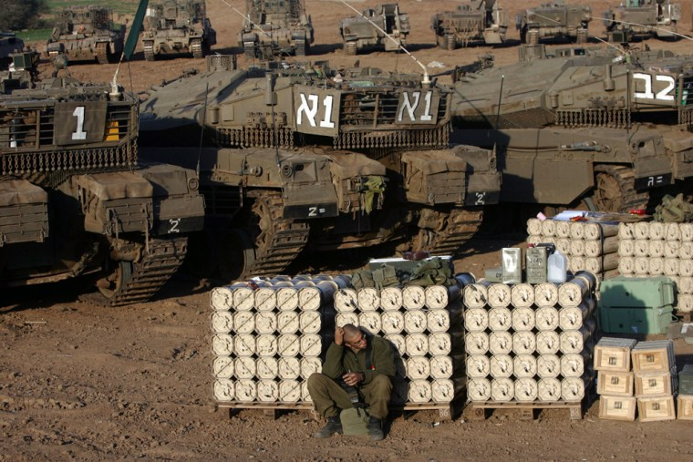 An Israeli soldier rests on Monday at a military staging area in southern Israel on the border with the Gaza Strip. A new truce appeared to be holding, stopping Palestinian rocket fire and Israeli operations in Gaza for the first time in five months, sparking hopes that it might lead to resumption of long-frozen peace negotiations.