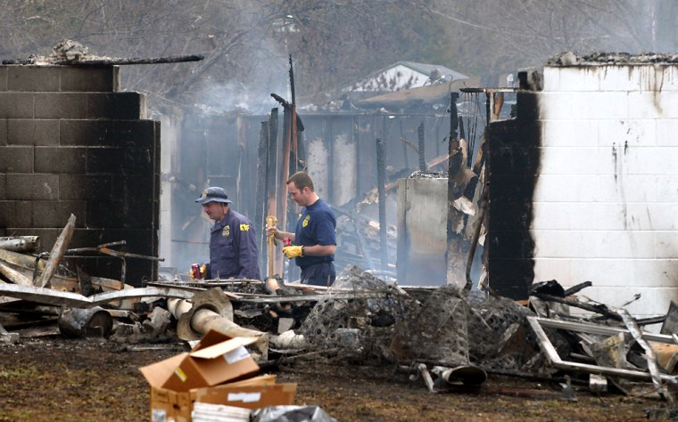 ATF officials look through the rubble left after a fire at a group home for the elderly and mentally ill in Anderson, Mo., onMonday.