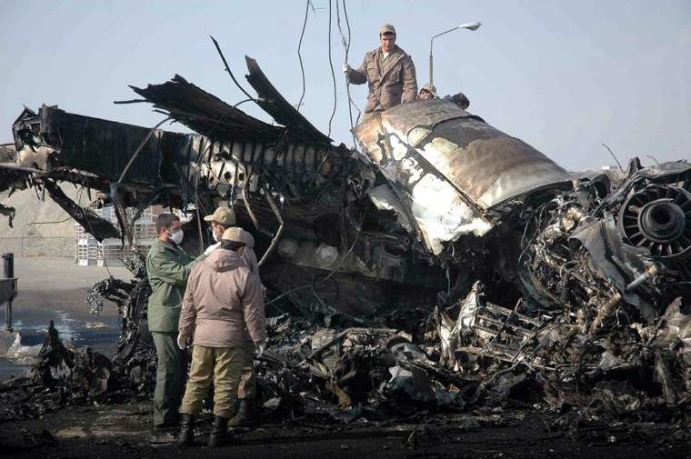 Iran's Revolutionary Guard soldiers assist atthe site of aplane crash at Tehran's Mehrabad airport on Monday.