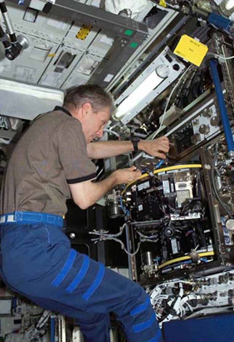 ESA astronaut Thomas Reiter works with the European Modular Cultivation System aboard the International Space Station. Astronauts aboard the space station are studying how zero gravity effects plant growth and human sleep patterns, among other experiments.