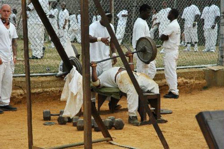 Inmates lift weights in the prison yard as a means to stay in shape and look good if they ever get out of Holman.