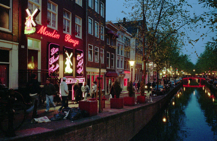 "Neon lights and sex shops dot a street in Amsterdam's Red Light district in this May 1996 file photo. The city is shutting down nearly one-third of the 350 prostitution ""windows"" in the neighborhood as part of a crackdown on crime."