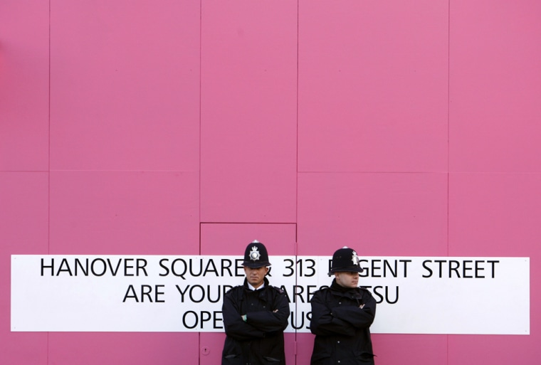 Policemen stand guard outside the Itsu restaurant in the Piccadilly area of central London