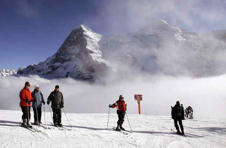 Ski tourists enjoy the sun on top of the Lauberhorn mountain, backdropped by the Eiger, left, and Moench mountains in Wengen, Switzerland.