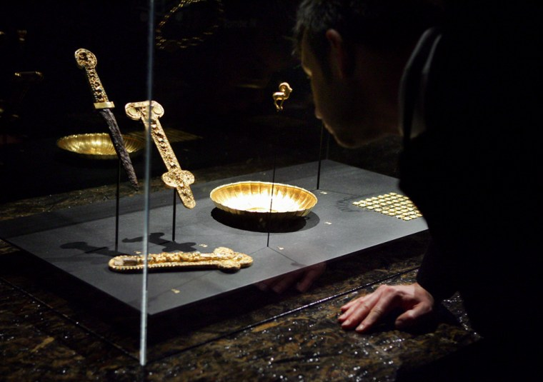 Visitors take a look at some of the glittering items presented at Guimet Museum in Paris on Monday, as part of an exhibition of Afghanistan's treasures. These gold items were hidden away for years, by brave art lovers who defied the Taliban and risked their lives to save them.