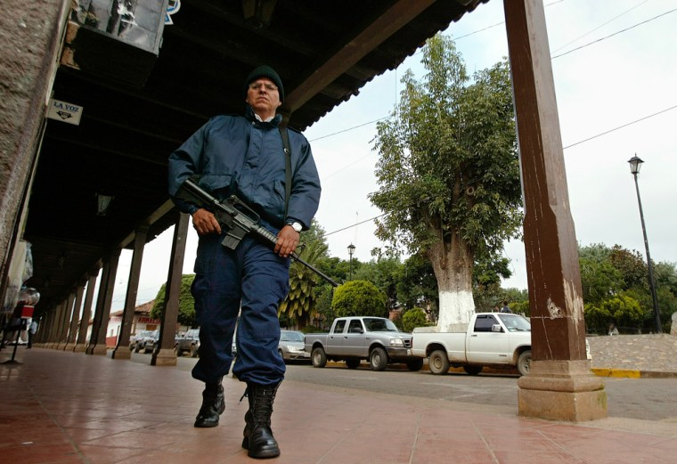 A police officer walks in the Central State of Michoacan, Mexico on Monday, part of a force of more than 6,500 soldiers and police sent by Mexico's new government to the western state of Michoacan to crack down on execution-style killings.