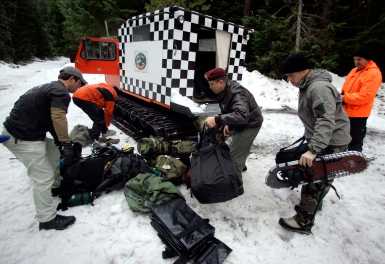 Members of a rescue team load a Snow Cat on Tuesday before searching for three climbers missing on Mount Hood, Ore. The three experienced climbers were reported missing in heavy snow Sunday.