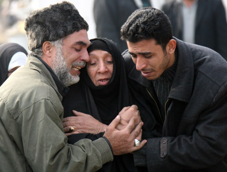 Iraqis cry at a Baghdad hospital on Wednesday after collecting the remains of a relative who was recently killed.