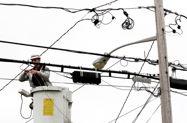 Joe DeBonis, a Verizon lineman, connects fiber optic cable that will serve a home in a North Bellmore, N.Y.Verizon expects its FiOs TV service will be available to 1 million homes by January 2007.
