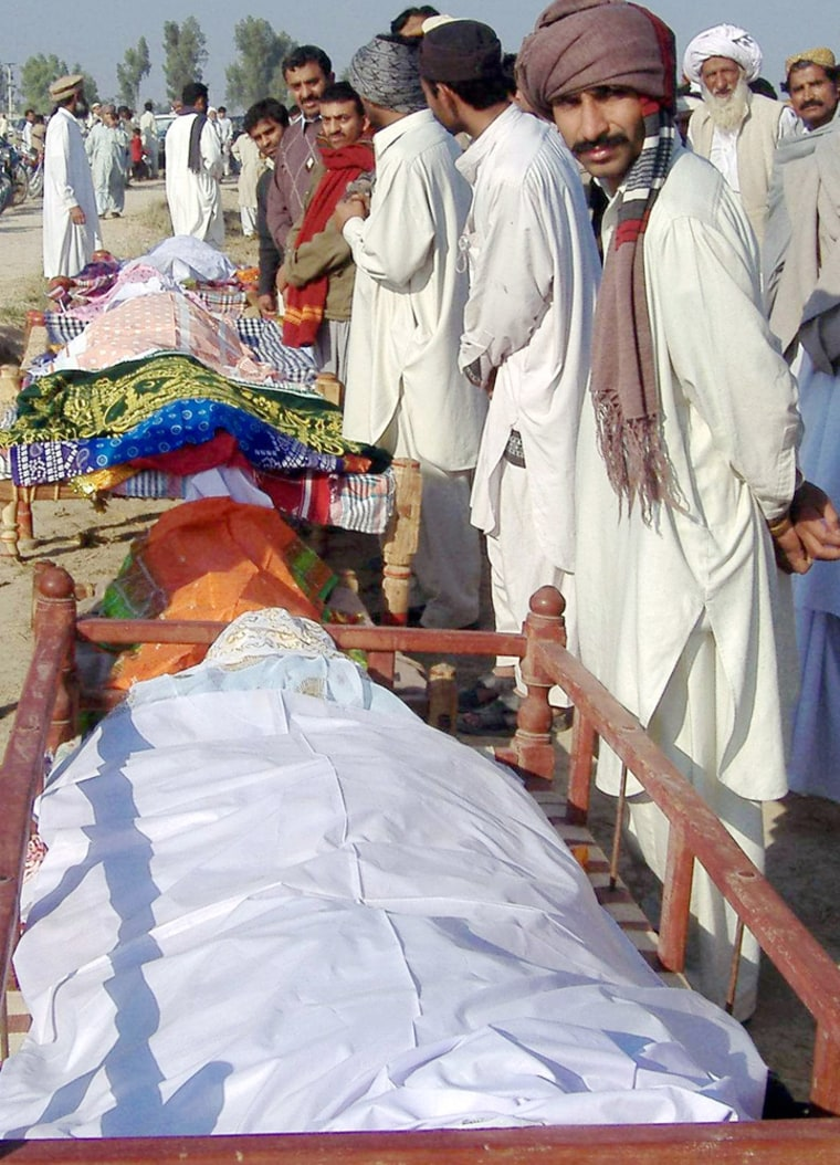 Relatives and residents stand beside the coffins of the stampede victims during a funeral in Jhok Utra village, Pakistan.
