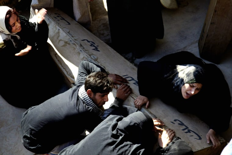 Iraqis mourn over the coffin of their re