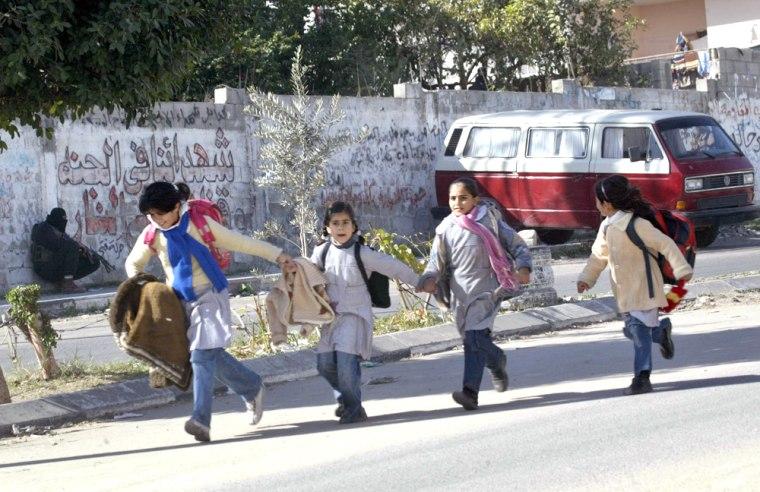 School girls run fleeing past an armed m