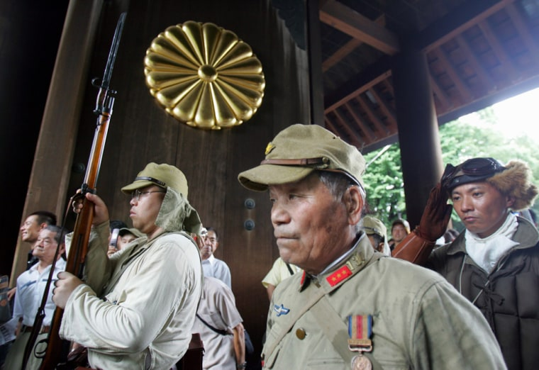 Japanese men in military costumes pay respects to the nation's war dead at the Yasukuni Shrine in Tokyo on Aug. 15, 2006.