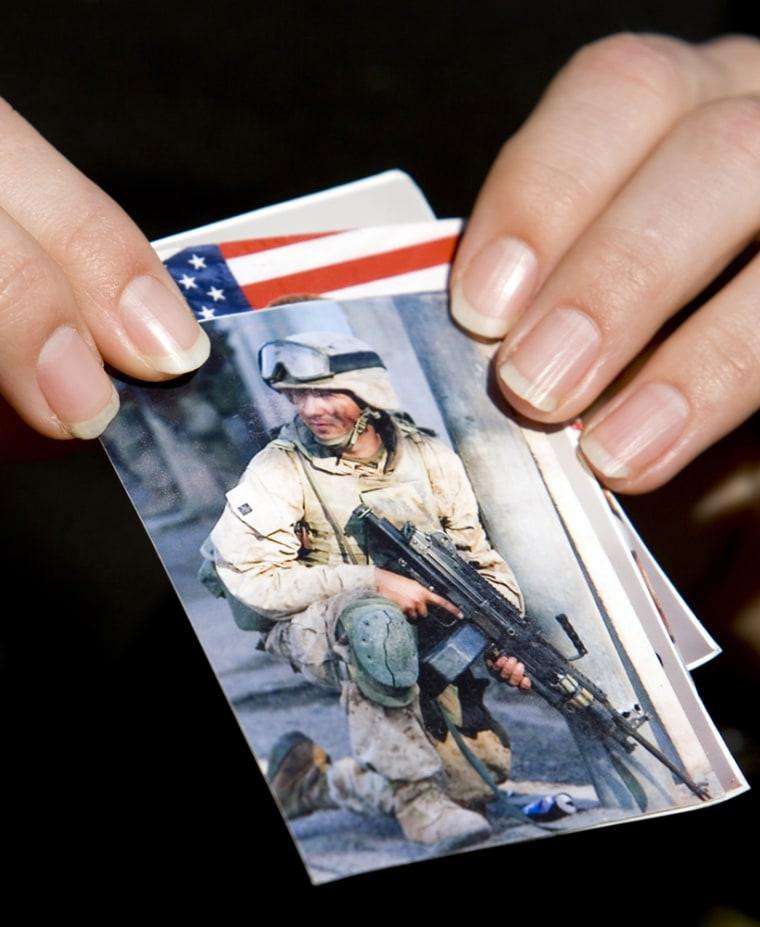Jaclyn Sharratt holds photos of her brother US Marine Lance Corporal Justin Sharratt before Haditha news briefing at US Marine Camp Pendleton