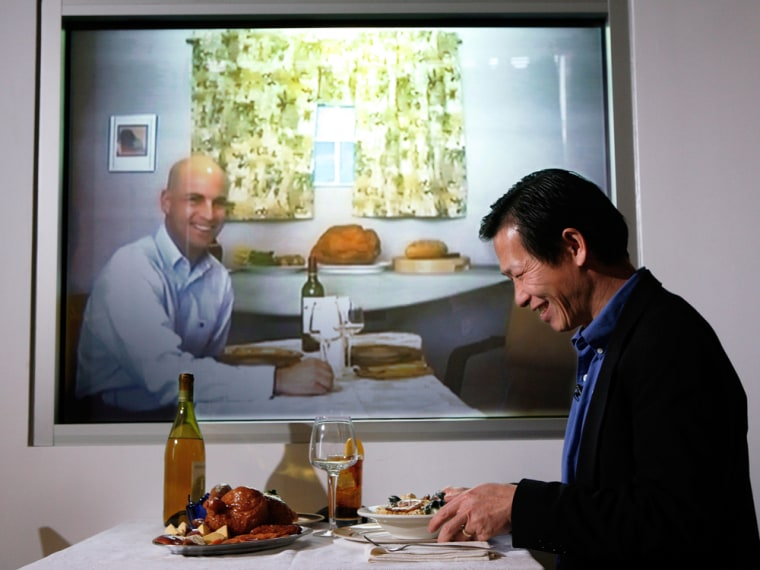 Accenture researchers Dadong Wan, right, and Adam Pilon, on screen, demonstrate a video-conferencing device that allows families to dine together from different locations.