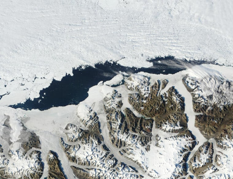 This NASA satellite image shows the Ayles Ice Shelf collapse, center and below the open water, on Aug. 13, 2005. Within days of breaking free and becoming an island,Ayles drifted about 30 miles before freezing into the sea ice seen here along top of photo.